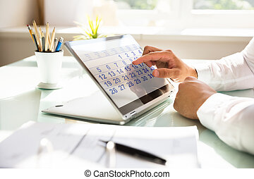 Businessman using calendar on laptop