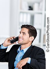 Businessman Using Cordless Phone While Looking Up