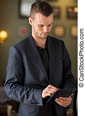Businessman Using Digital Tablet At Cafe