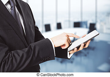 Businessman using digital tablet in empty conference room