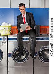 Businessman Using Digital Tablet In Laundry