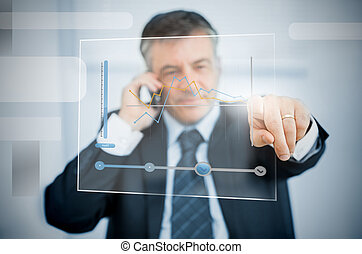 Businessman using futuristic touchscreen to view graph