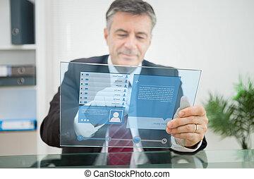 Businessman using futuristic touchscreen to view social...