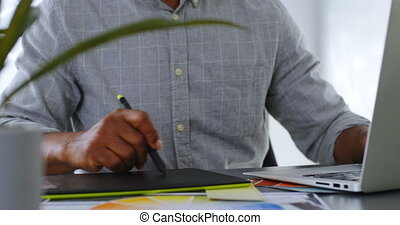 Businessman using graphic tablet on desk at office 4k