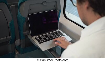 Businessman using his laptop on his way to work on the train