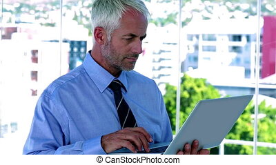 Businessman using his tablet and sm