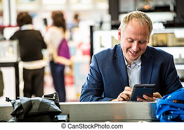 Businessman using his tablet at the airport