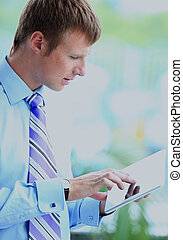 Businessman using his tablet in the office.