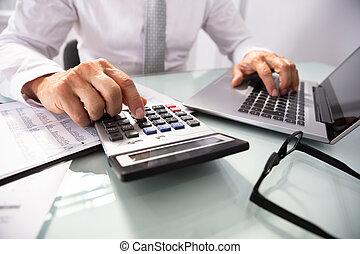 Businessman Using Laptop And Calculator