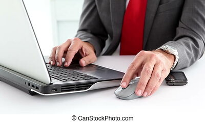 Businessman using laptop and typing