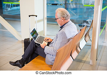 Businessman Using Laptop At Airport Terminal