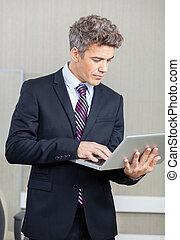 Businessman Using Laptop At Call Center