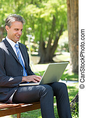 Businessman using laptop at park