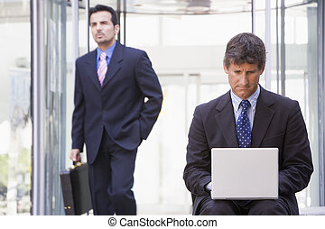 Businessman using laptop computer outside