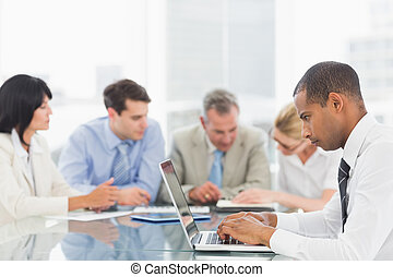 Businessman using laptop during a meeting