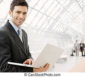 Businessman using laptop - Happy young businessman using...