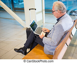 Senior businessman using laptop while waiting for flight at airport