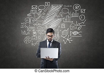 Businessman using laptop in front of blackboard with icons