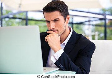 Businessman using laptop in restaurant
