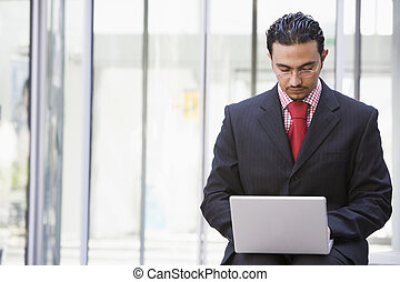 Businessman using laptop outside