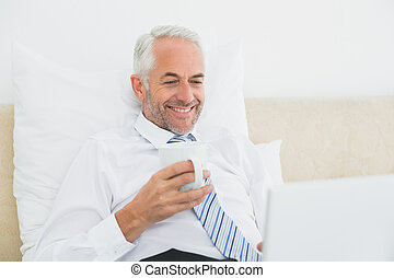 Businessman using laptop while having coffee in bed