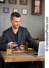 Businessman Using Laptop While Having Food In Restaurant
