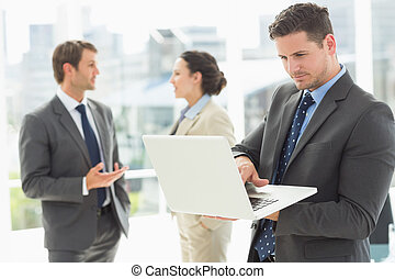 Businessman using laptop with colleagues discussing in office