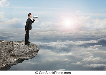 Businessman using megaphone yelling on cliff with sunlight...
