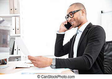 Businessman using mobile phone and looking at documents -...