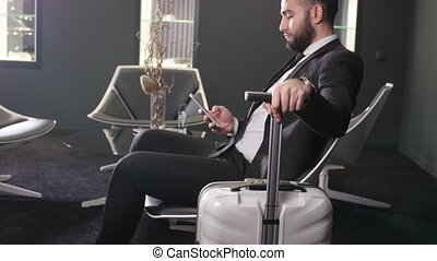 Businessman using mobile phone at the airport in the waiting lounge