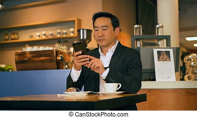 Businessman using mobile phone in cafe 4k - Young ...