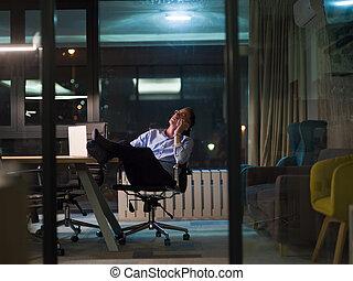 businessman using mobile phone in dark office