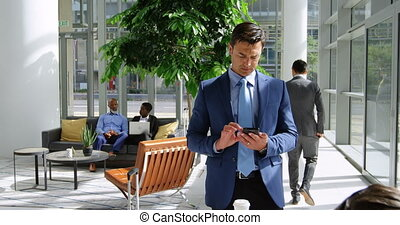 Businessman using mobile phone in the lobby 4k - Businessman...
