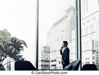 Businessman using mobile phone near office window at corridor area,tone filter photo
