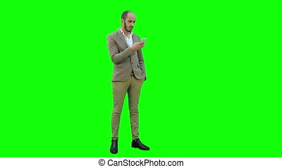 Businessman using mobile phone on a Green Screen, Chroma Key.