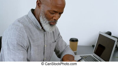 Businessman using mobile phone on desk 4k