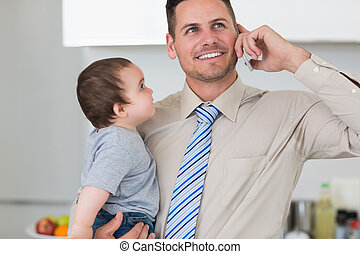 Businessman using mobile phone while carrying baby -...
