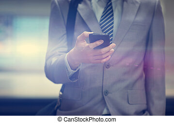 Businessman using smart phone at train station.