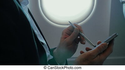 Businessman using smart phone during the flight