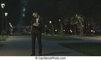 Businessman using smart phone make a call while standing at park in a city square, and make notes.