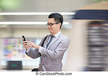 Businessman using smartphone at subway.