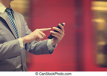 Businessman using smartphone at train station.