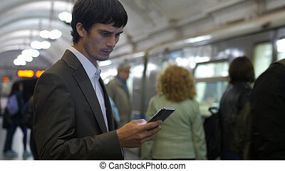 Businessman Using Smartphone on in Subway
