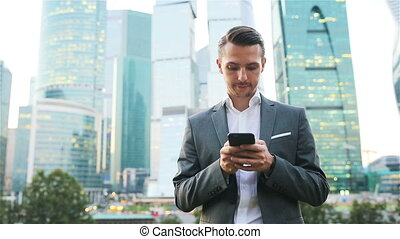 Young caucasian man holding smartphone for business work.