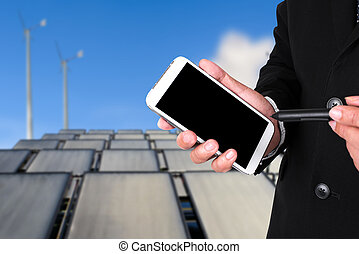 Businessman using smartphone with background Solar panels and wind turbine against blue sky