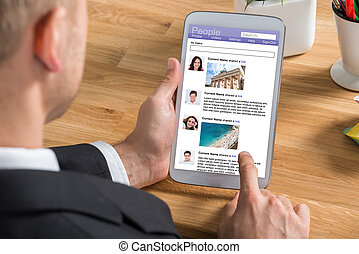 Businessman Using Social Networking Site On Digital Tablet