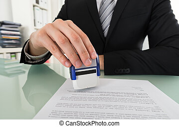 Businessman Using Stamper On Document
