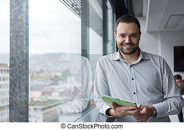 Businessman Using Tablet In Office Building by window -...