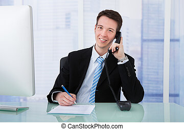 Businessman Using Telephone While Writing On Document At Desk