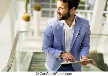 Businessman using touchscreen tablet in modern office
